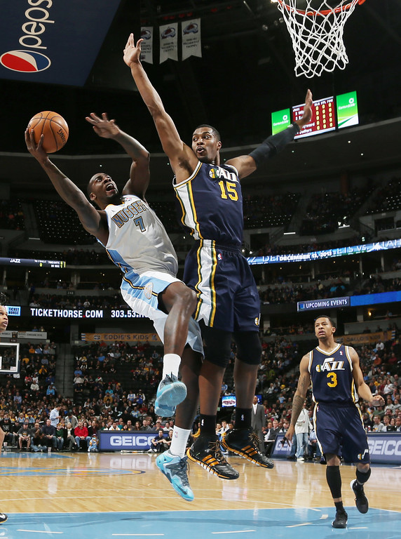 . Denver Nuggets forward J.J. Hickson, front left, is fouled as he goes up for a shot by Utah Jazz center Derrick Favors, front right, as Jazz guard Trey Burke trails the play in the first quarter of an NBA basketball game in Denver on Friday, Dec. 13, 2013. (AP Photo/David Zalubowski)