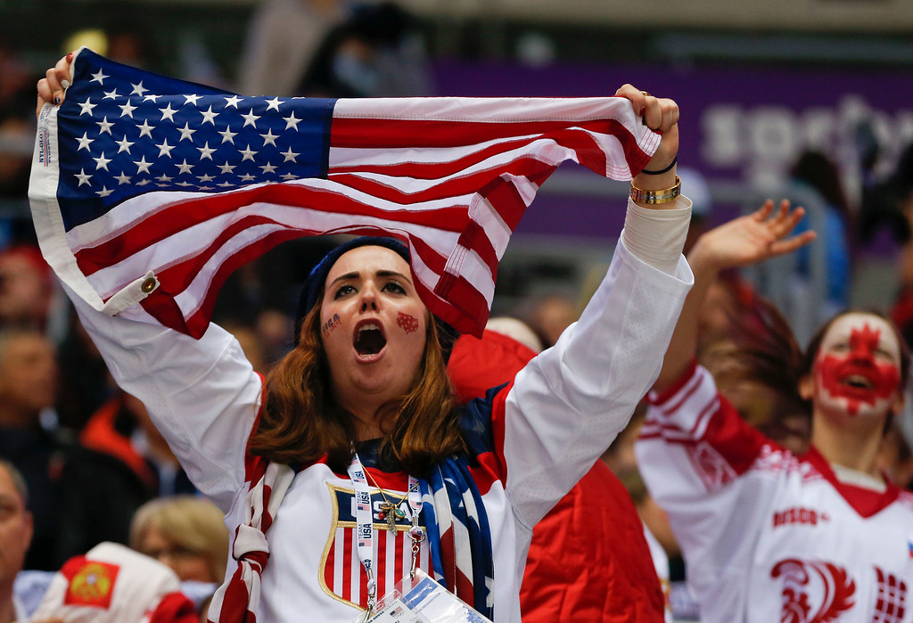 . American and Canadian hockey fans cheer as Canada and the USA warm up before playing in a men\'s semifinal ice hockey game at the 2014 Winter Olympics, Friday, Feb. 21, 2014, in Sochi, Russia. (AP Photo/Petr David Josek)