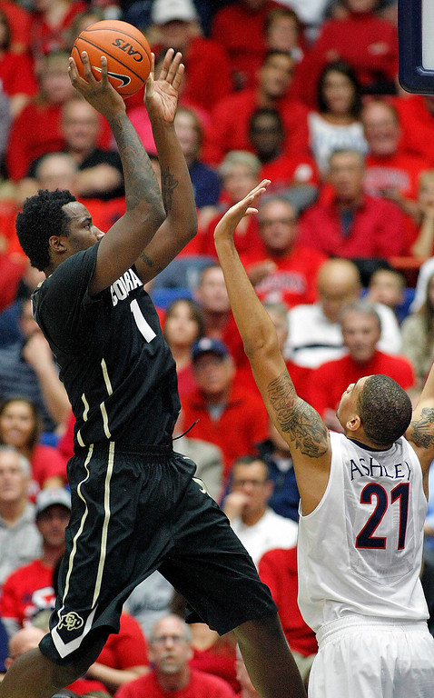 . Colorado\'s Wesley Gordon (1) shoots for two over the arms of Arizona\'s Brandon Ashley (21) in the first half of an NCAA college basketball game, Thursday, Jan. 23, 2014 in Tucson, Ariz. (AP Photo/John Miller)