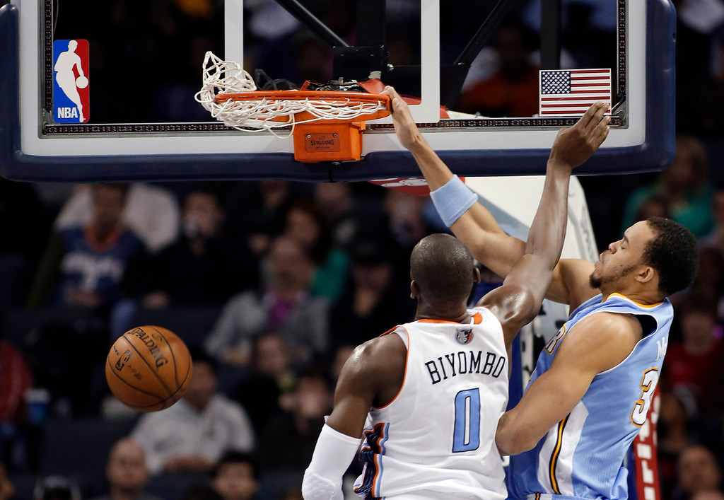 . Denver Nuggets\' JaVale McGee (34) dunks over Charlotte Bobcats\' Bismack Biyombo (0) during the first half of an NBA basketball game in Charlotte, N.C., Saturday, Feb. 23, 2013. (AP Photo/Bob Leverone)