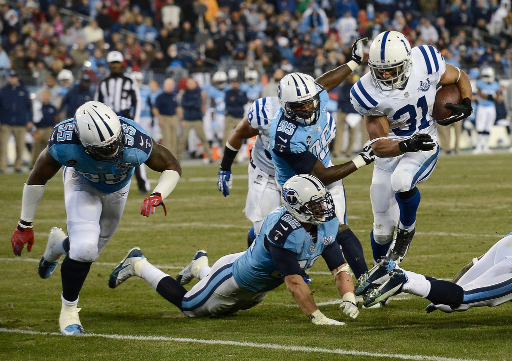 . Indianapolis Colts running back Donald Brown (31) scores a touchdown on a 6-yard run against the Tennessee Titans in the third quarter of an NFL football game Thursday, Nov. 14, 2013, in Nashville, Tenn. Defending for the Titans are Zach Brown (55), Colin McCarthy (52) and Kamerion Wimbley (95). (AP Photo/Mark Zaleski)