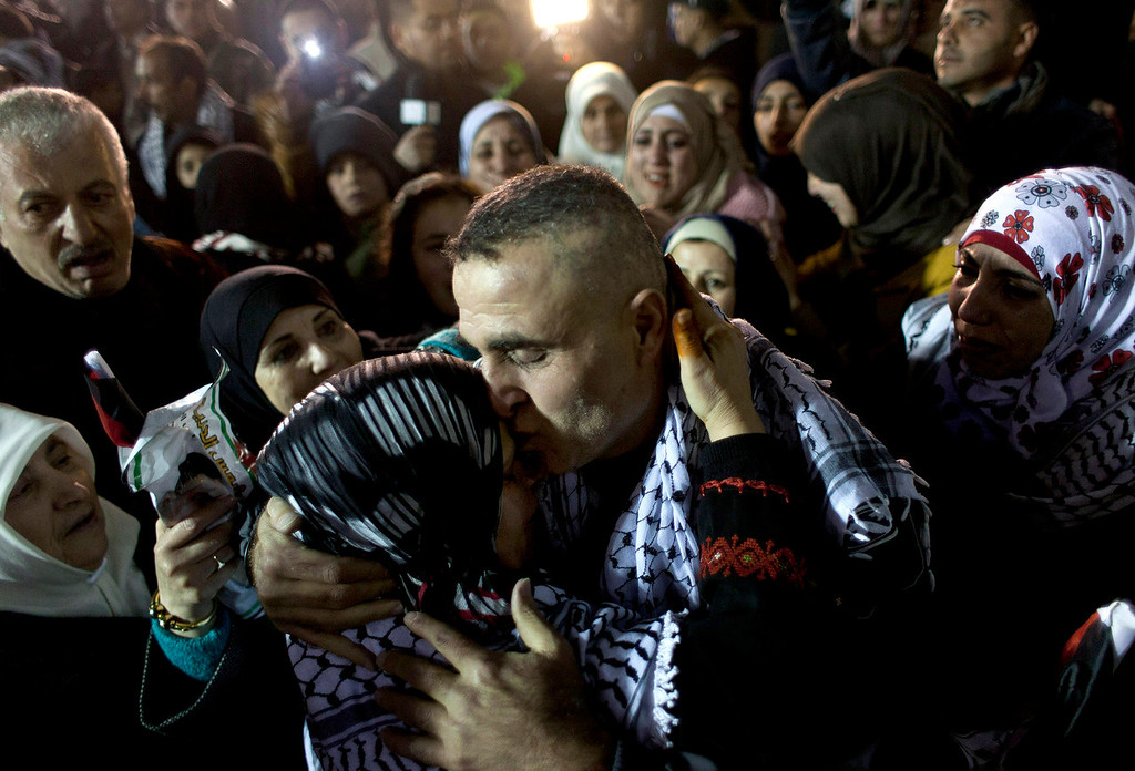 . A released Palestinian prisoner is received by his family following a welcome ceremony and celebrations after arriving at the Palestinian headquarters in the West Bank city of Ramallah, Tuesday, Dec. 31, 2013. Israel released more than two dozen Palestinian prisoners convicted in deadly attacks against Israelis early Tuesday as part of a U.S.-brokered package to restart Mideast peace talks. (AP Photo/Nasser Nasser)