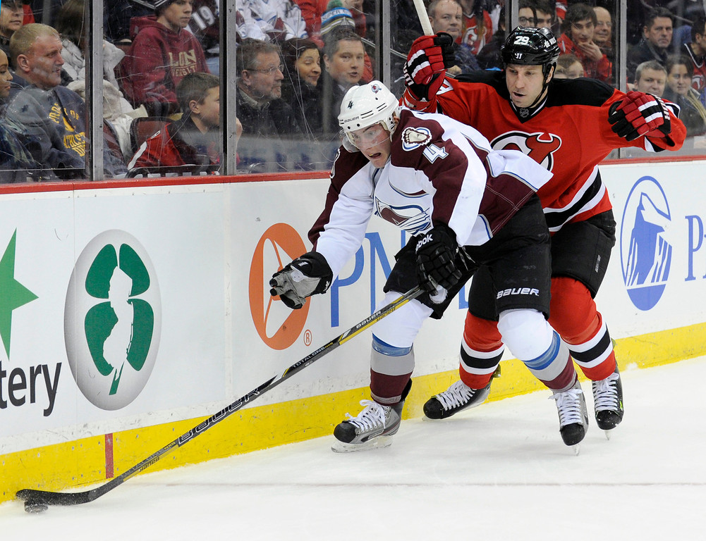 . Colorado Avalanche\'s Tyson Barrie controls the puck as he is checked by New Jersey Devils\' Ryan Clowe, right, during the second period of an NHL hockey game Monday, Feb. 3, 2014, in Newark, N.J. (AP Photo/Bill Kostroun)