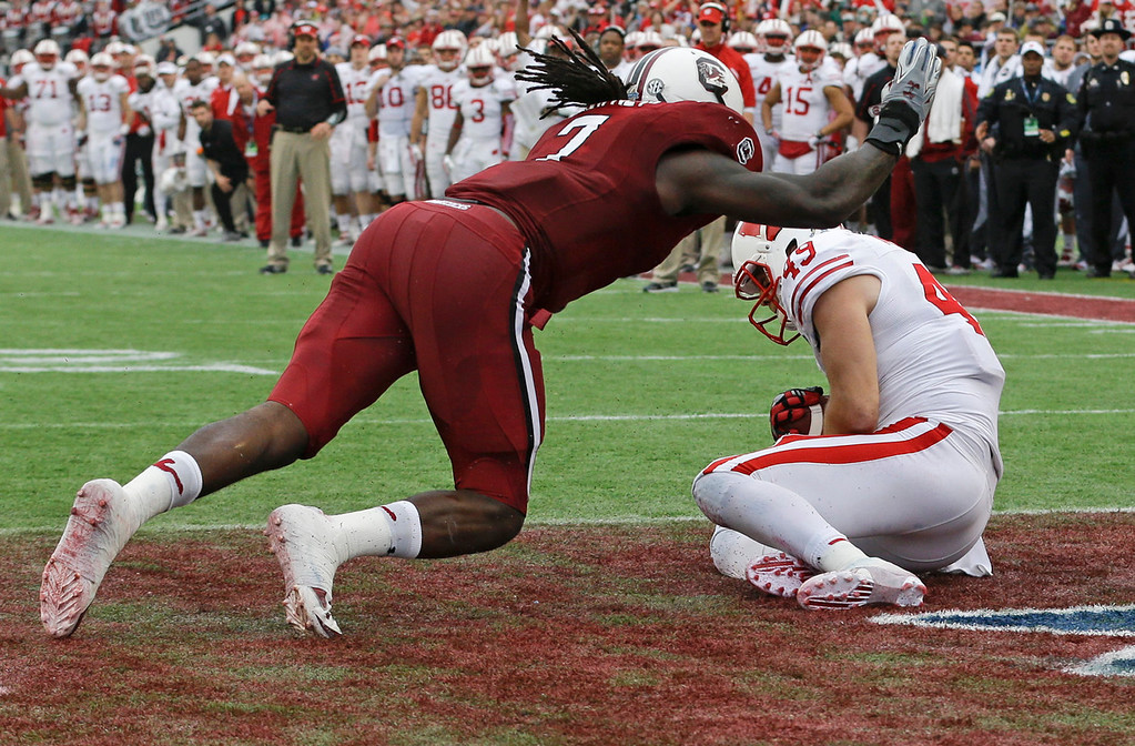 . Wisconsin tight end Sam Arneson (49) catches a pass for a touchdown in front of South Carolina defensive end Jadeveon Clowney, left, during the first half of the Capital One Bowl NCAA college football game in Orlando, Fla., Wednesday, Jan. 1, 2014.(AP Photo/John Raoux)