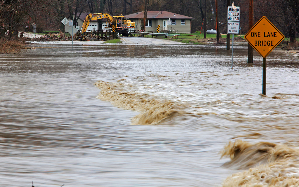 . Road crews begin clearing debris collecting on a bridge along Herber Road north of Dubuque, Iowa, as flash flooding completely closed the section of road Thursday April 18, 2013.  (AP/TELEGRAPH HERALD/mbr)