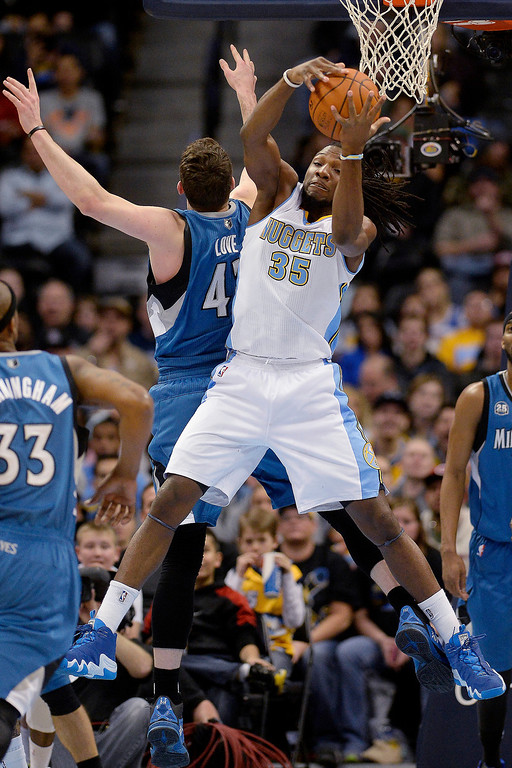 . Kenneth Faried (35) of the Denver Nuggets grabs a rebound from Kevin Love (42) of the Minnesota Timberwolves during the first quarter at the Pepsi Center.   (Photo By AAron Ontiveroz/The Denver Post)