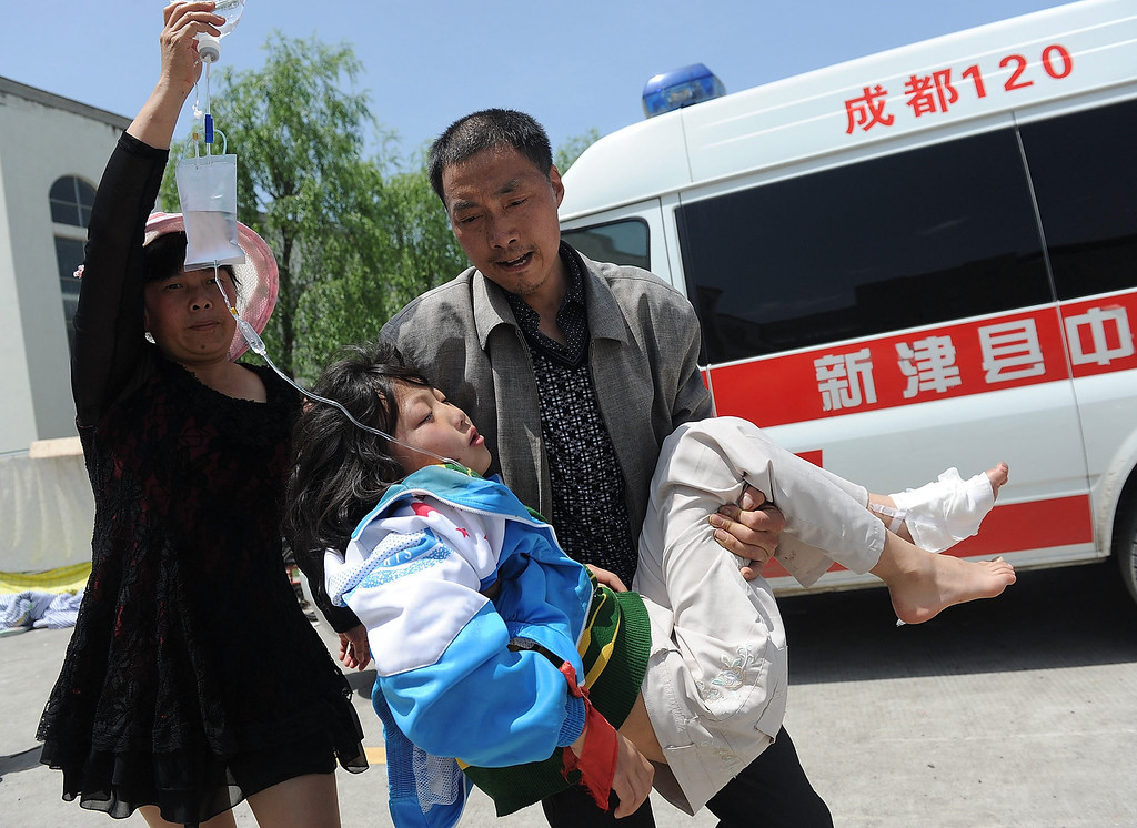 . A man carries an injured woman to a temporary treatment station following an earthquake in Lushan county in Ya\'an in southwest China\'s Sichuan province Saturday, April 20, 2013. The powerful earthquake shook Chinaís Sichuan province Saturday morning, nearly five years after a devastating quake jolted the province. (AP Photo)