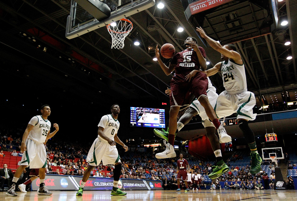 . DAYTON, OH - MARCH 19: D\'Angelo Scott #15 of the Texas Southern Tigers and Jamal Johnson #24 of the Cal Poly Mustangs go for a rebound during the first round of the 2014 NCAA Men\'s Basketball Tournament at UD Arena on March 19, 2014 in Dayton, Ohio.  (Photo by Gregory Shamus/Getty Images)