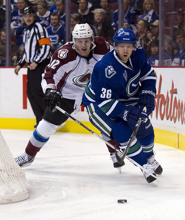 . Jannik Hansen #36 of the Vancouver Canucks chases after a loose puck as Gabriel Landeskog #92 of the Colorado Avalanche trails theplay during the first period in NHL action on March 28, 2013 at Rogers Arena in Vancouver, British Columbia, Canada.  (Photo by Rich Lam/Getty Images)