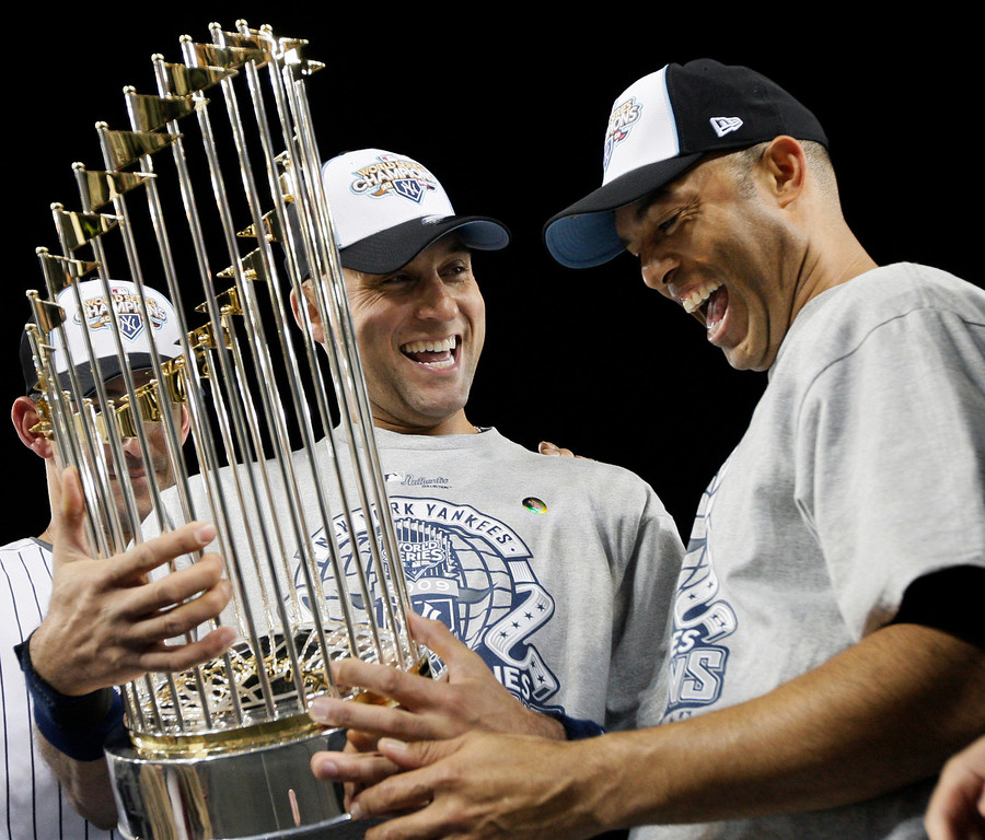 . In this Nov. 4, 2009 file photo, New York Yankees\' Derek Jeter, left, and Mariano Rivera look at the championship trophy after winning the Major League Baseball World Series against the Philadelphia Phillies, in New York. (AP Photo/David J. Phillip, File)
