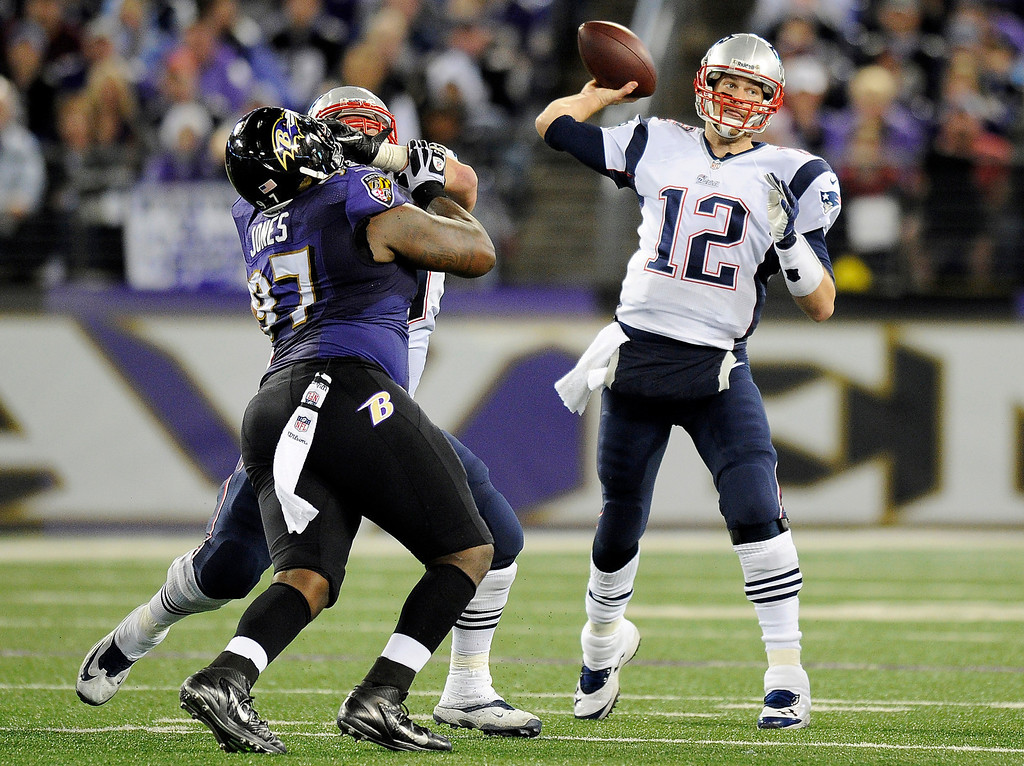 . New England Patriots quarterback Tom Brady (12) throws to a receiver as he is pressured by Baltimore Ravens defensive end Arthur Jones, left, in the first half of an NFL football game, Sunday, Dec. 22, 2013, in Baltimore. (AP Photo/Nick Wass)