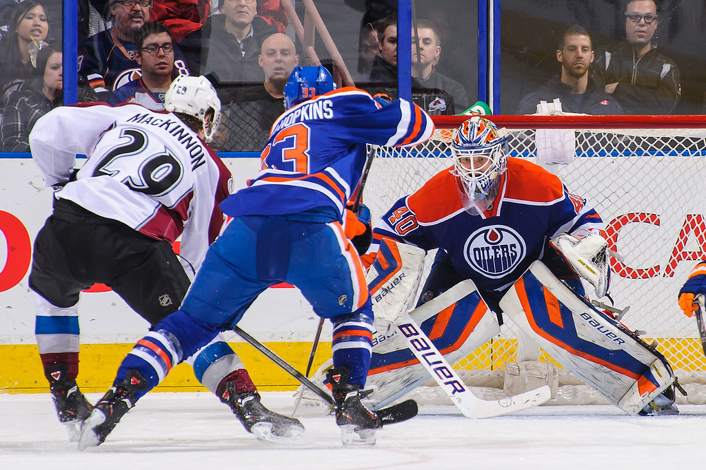 . EDMONTON, AB - DECEMBER 5: Ryan Nugent-Hopkins #93 and Devan Dubnyk #40 of the Edmonton Oilers defend against Nathan MacKinnon #29 of the Colorado Avalanche during an NHL game at Rexall Place on December 5, 2013 in Edmonton, Alberta, Canada. (Photo by Derek Leung/Getty Images)