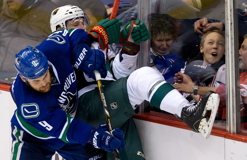 . A young fan reacts as Vancouver Canucks\' Zack Kassian, left, checks Minnesota Wild\'s Erik Haula during the second period of an NHL hockey game Friday, Feb. 28, 2014, in Vancouver, British Columbia. (AP Photo/The Canadian Press, Darryl Dyck)