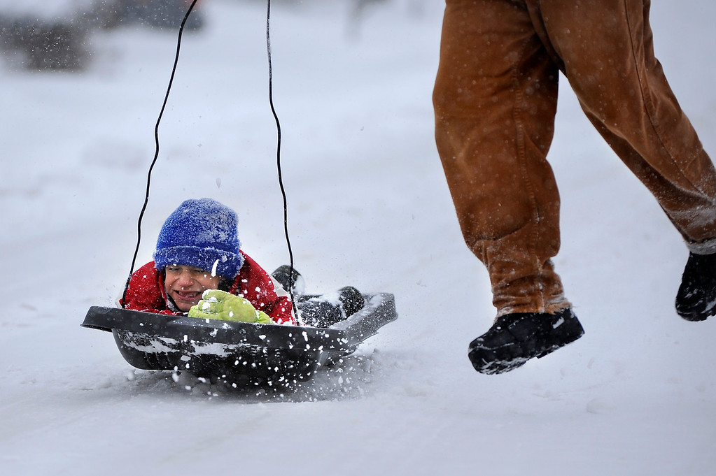 . Jeremiah Good, 7, feels the pull as his father Dave sends him off near their home after an overnight snow storm left several inches in Arvada, Colorado on Friday, February 3,  2012. Joe Amon, The Denver Post