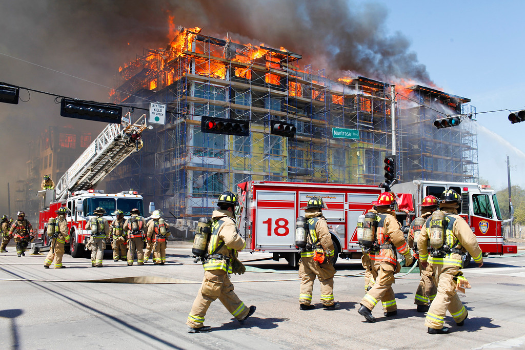 . Houston firefighters work to extinguish a five-alarm fire at a construction site Tuesday, March 25, 2014, in Houston. Fire officials said more than 200 emergency personnel were at the scene Tuesday afternoon and were working to protect nearby buildings. (AP Photo/Houston Chronicle, Eric Kayne)