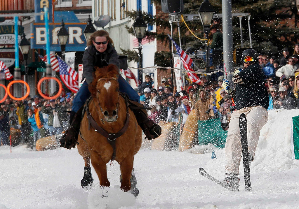 . A horserider pulls a skier down the snow-covered main street during the annual skijoring race in downtown Leadville, Colorado March 2, 2013. This was the 62nd year for the competition in Leadville.  REUTERS/Rick Wilking