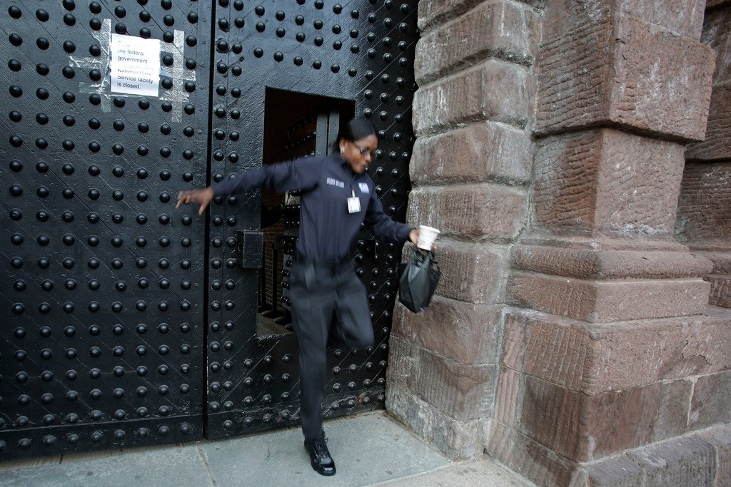 """. A government employee steps out of an opening in a door at Castle Clinton National Monument in lower Manhattan, Tuesday, Oct. 1, 2013 in New York. Congress plunged the nation into a partial government shutdown Tuesday as a long-running dispute over President Barack Obama\'s health care law forced about 800,000 federal workers off the job, suspending all but essential services.  \""""Closed\"""" signs and barricades sprang up at the Lincoln Memorial, and national parks and federal workplaces across the country were following suit. (AP Photo/Mark Lennihan)"""