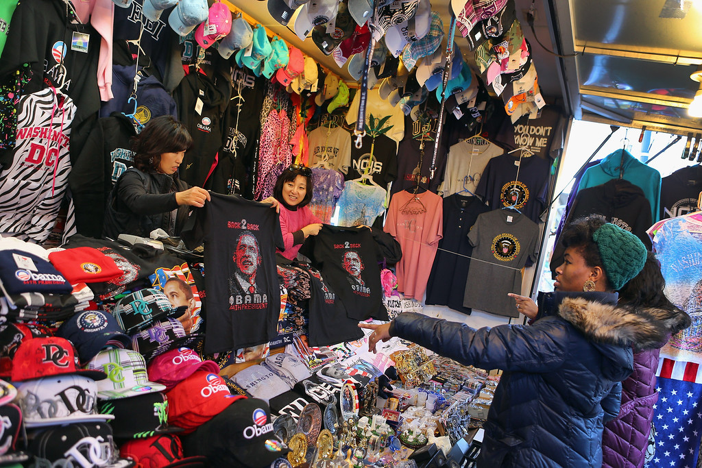 . Souvenir vendor holds a tee-shirt as preparations continue for the Presidential Inauguration on January 20, 2013 in Washington, DC.  The U.S. capital is preparing for the second inauguration of U.S. President Barack Obama, which will take place on January 21.  (Photo by Joe Raedle/Getty Images)