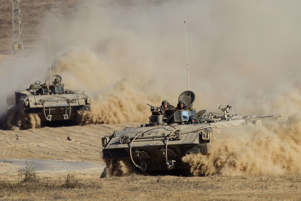 . Israeli army armored personnel carriers (APC) move along Israel\'s border with the Gaza Strip on July 30, 2014. Israel agreed to observe a four-hour lull in Gaza several hours after a deadly strike on a school killed 16, drawing a furious response from a UN refugee agency. AFP PHOTO/ JACK GUEZ/AFP/Getty Images