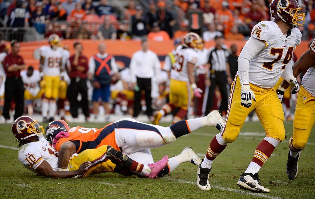 . Denver Broncos defensive tackle Terrance Knighton (94) takes Washington Redskins quarterback Robert Griffin III (10) to the turf during the fourth quarter. Griffin did not return to the game. The Denver Broncos vs. the Washington Redskins at Sports Authority Field at Mile High in Denver on October 27, 2013. (Photo by Tim Rasmussen/The Denver Post)