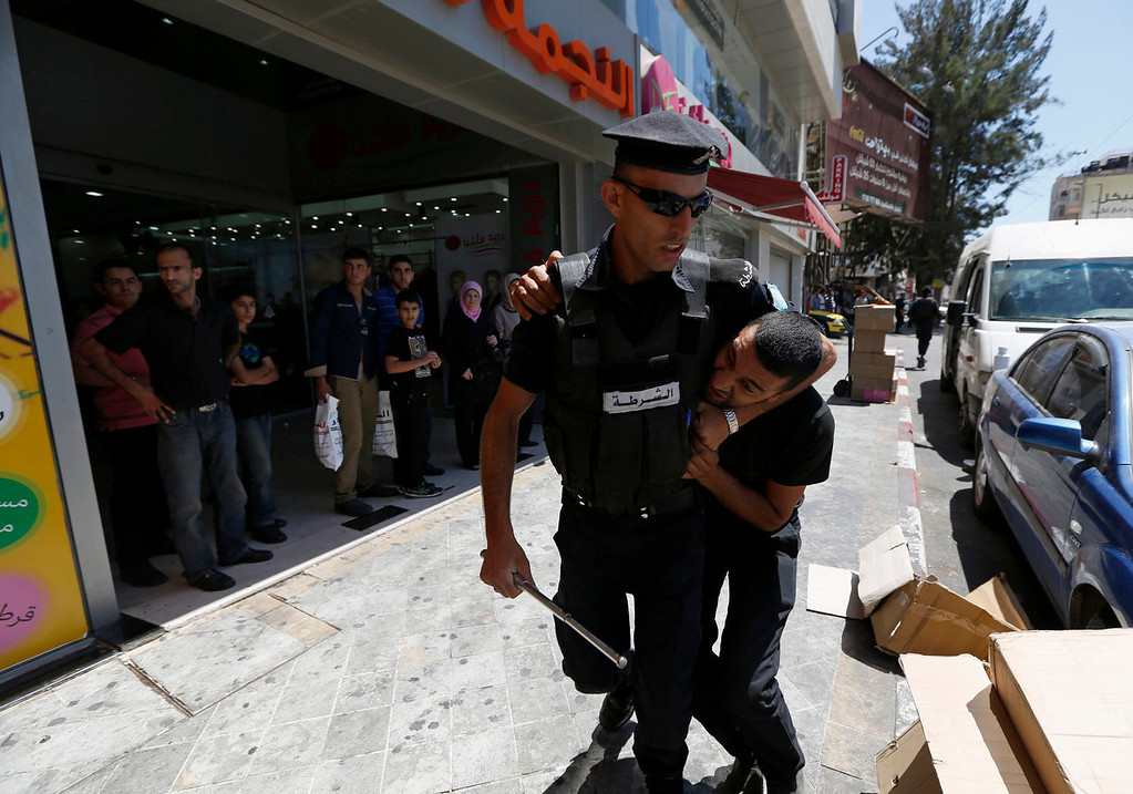 . A Palestinian policeman detains a protester during a demonstration against the renewal of stalled peace talks with Israel, in the West Bank city of Ramallah, July 28, 2013. Israel was expected on Sunday to approve releasing more than 100 Arab prisoners as a step to renew stalled peace talks with the Palestinians ahead of plans to convene negotiators in Washington later this week. REUTERS/Mohamad Torokman