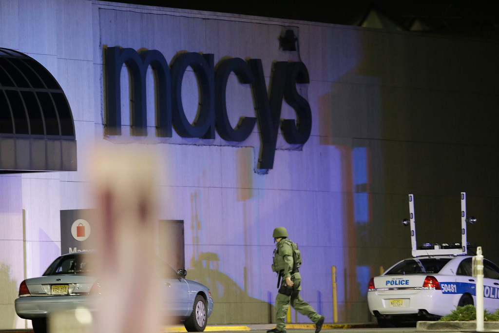 . An official wearing tactical gear walks outside of Garden State Plaza Mall following reports of a shooter, Monday, Nov. 4, 2013, in Paramus, N.J. Hundreds of law enforcement officers converged on the mall Monday night after witnesses said multiple shots were fired there. (AP Photo/Julio Cortez)