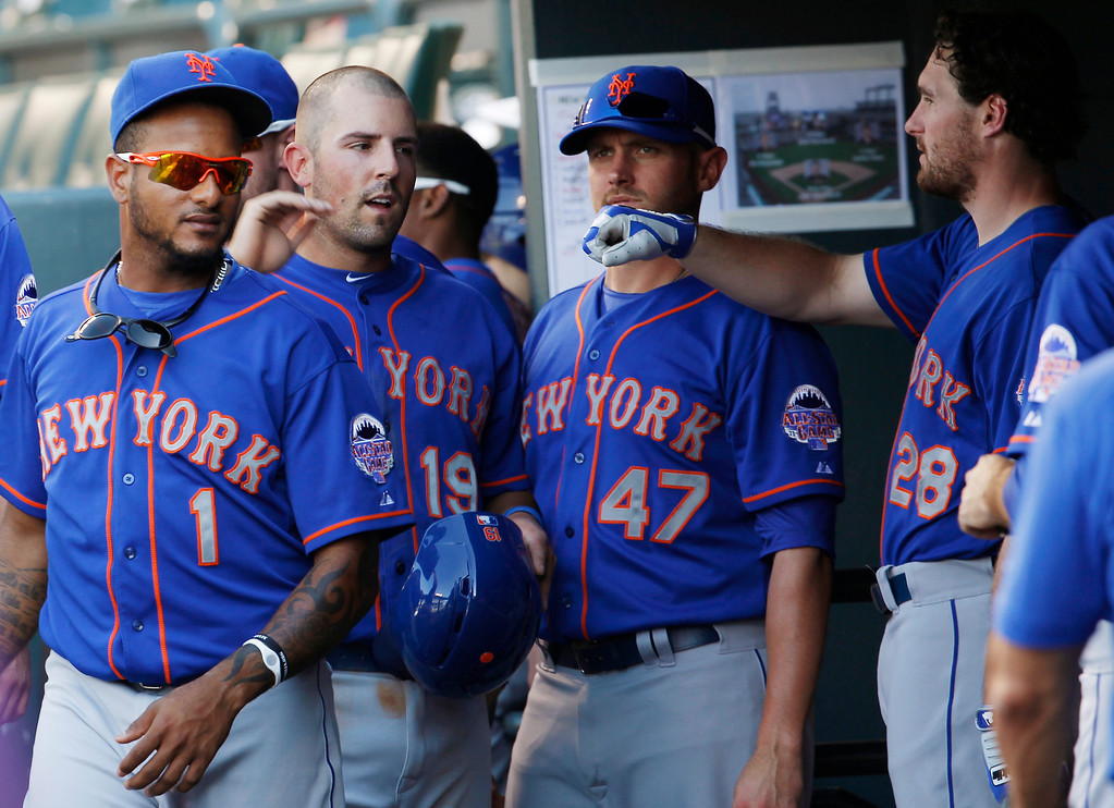 . New York Mets\' Zach Lutz, second from left, is congratulated by teammates Jordany Valdespin (1), Andrew Brown and Daniel Murphy (28) after Lutz scored on a force play against the Colorado Rockies in the fifth inning of a baseball game in Denver on Thursday, June 27, 2013. (AP Photo/David Zalubowski)