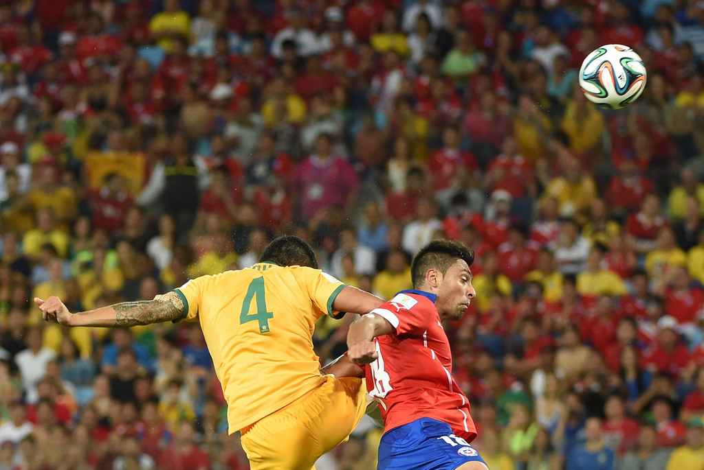 . Australia\'s forward Tim Cahill (L) and Chile\'s defender Gonzalo Jara vie for the ball during a Group B football match between Chile and Australia at the Pantanal Arena in Cuiaba during the 2014 FIFA World Cup on June 13, 2014.     AFP PHOTO / WILLIAM WEST