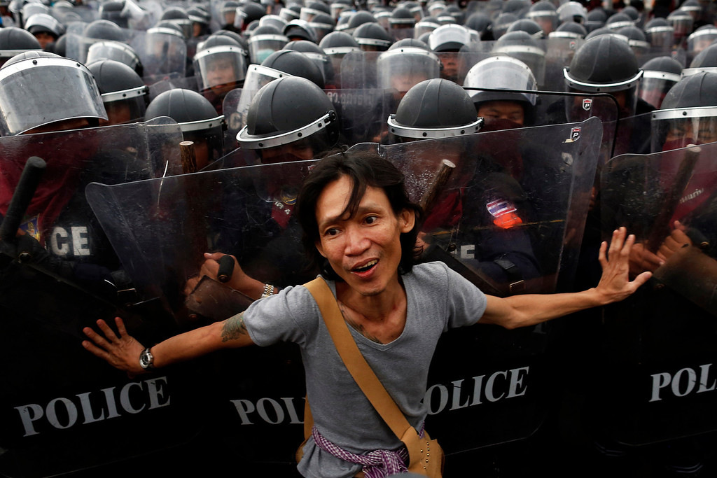 . An anti-government protester pushes riot police officers during scuffles near the Government house in Bangkok November 24, 2012. Thai police fired tear gas to disperse hundreds of anti-government protesters who pushed through barriers and clashed with security forces as thousands gathered seeking to overthrow Prime Minister Yingluck Shinawatra\'s government.   REUTERS/Damir Sagolj