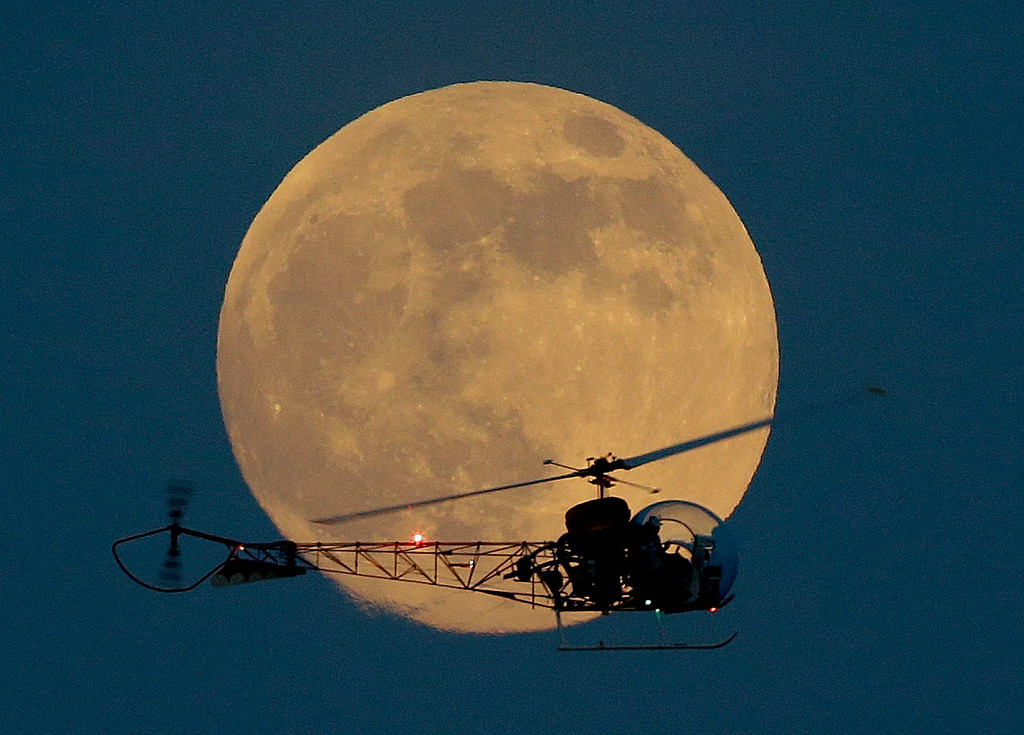 ". The moon is seen in its waxing gibbous stage as it rises behind the helicopter from the original Batman television show, which people can ride at the New Jersey State Fair, on Saturday, June 22, 2013, in East Rutherford, N.J. The moon, which will reach its full stage on Sunday, is expected to be 13.5 percent closer to Earth during a phenomenon known as a ""super moon\"".  (AP Photo/Julio Cortez)"