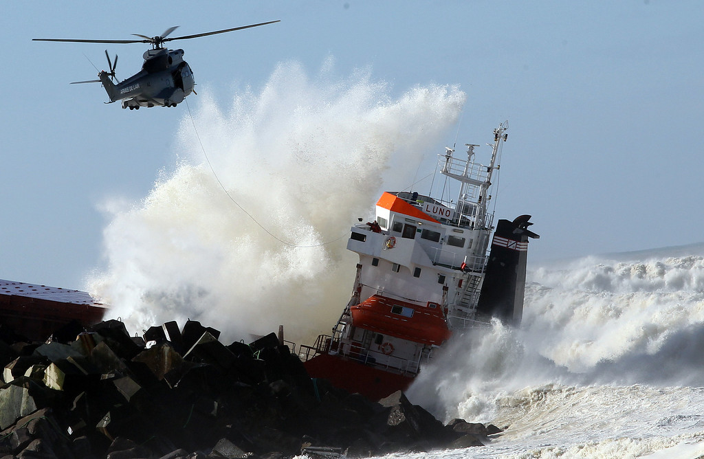 ". A military helicopter flies over a Spanish cargo ship ""Luno\"" that slammed into a jetty in choppy Atlantic Ocean waters and broke in two, off Anglet, southwestern France, Wednesday, Feb. 5, 2014. . (AP Photo/Bob Edme)"