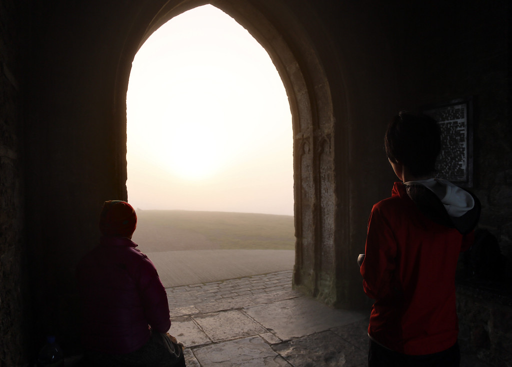 . Visitors to Glastonbury Tor meditate inside St. Michael\'s Tower, a ruined 14th-century church tower, as the rising sun begins to clear the early morning mist and fog near the town of Glastonbury on September 4, 2013 in Somerset, England. (Photo by Matt Cardy/Getty Images)