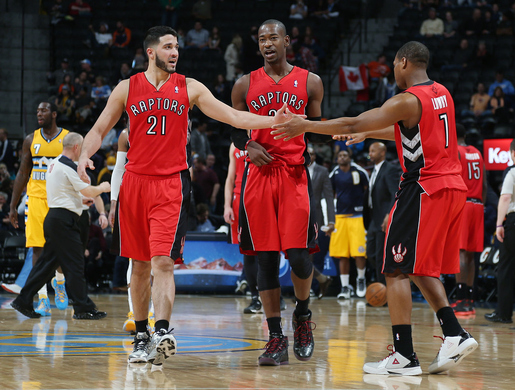 . From left to right, Toronto Raptors guards Greivis Vasquez, of Venezuela, celebrates with Terrence Ross and Kyle Lowry after their 100-90 victory over the Denver Nuggets in an NBA basketball game in Denver, Friday, Jan. 31, 2014. (AP Photo/David Zalubowski)