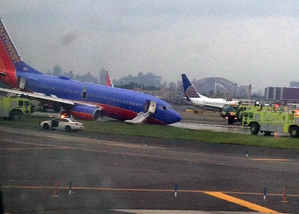 . A Southwest Airlines plane whose nose gear collapsed as it touched down on the runway is surrounded by emergency vehicles at LaGuardia Airport in New York on Monday, July 22, 2013. The plane was carrying 149 passengers and crew. (AP Photo/Courtesy of Jared Rosenstein)