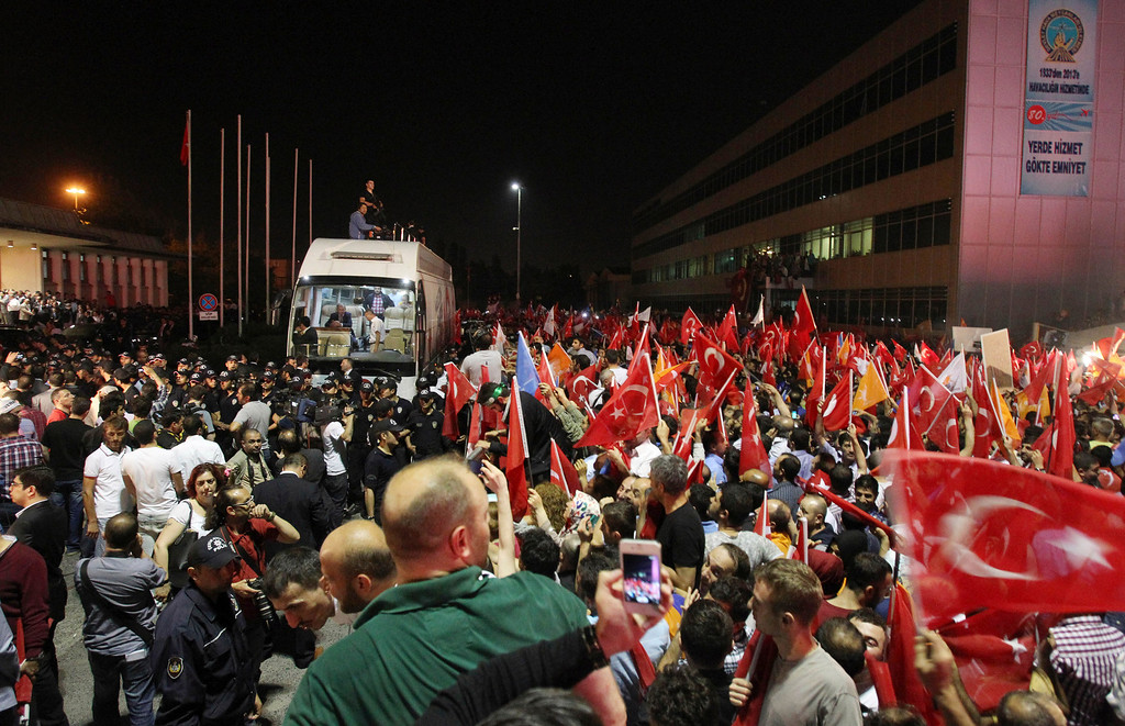 . The crowd cheers for Turkish Prime Minister Recep Tayyip Erdogan\'s arrival at the Ataturk Airport of Istanbul early Friday, June 7, 2013. Erdogan took a combative stance on his closely watched return to the country early Friday, telling supporters who thronged to greet him that the protests that have swept the country must come to an end. (AP Photo/Thanassis Stavrakis)
