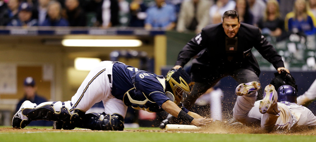 . Milwaukee Brewers catcher Martin Maldonado, left, tags out Colorado Rockies\' Carlos Gonzalez, right, at home plate during the eighth inning of a baseball game, Wednesday, April 3, 2013, in Milwaukee. Umpire Tony Randazzo watches the play. (AP Photo/Jeffrey Phelps)