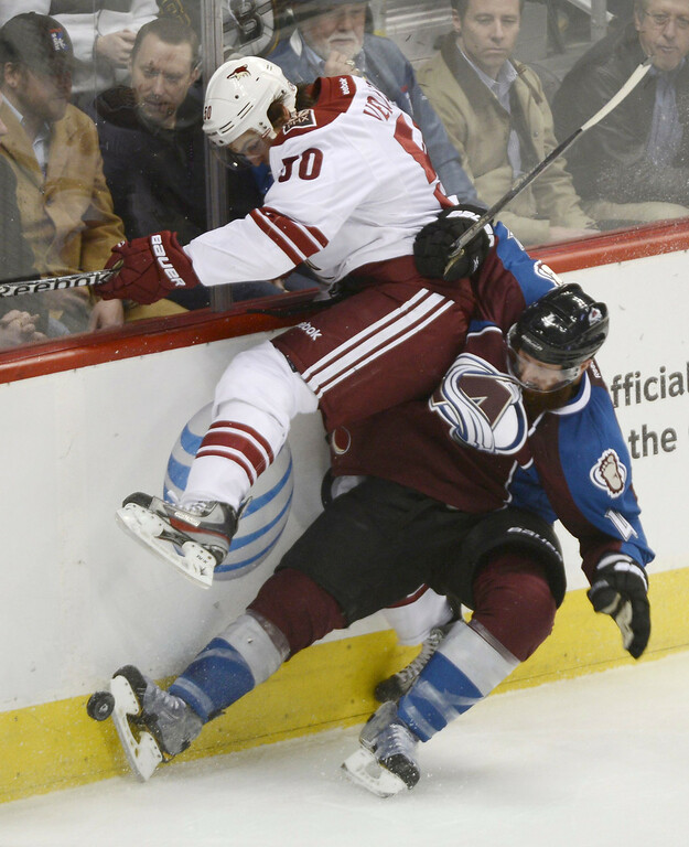 . DENVER, CO. - FEBRUARY 11: Greg Zanon (4) of the Colorado Avalanche collides with Antoine Vermette (50) of the Phoenix Coyotes along the boards during the second period February 11, 2013 at Pepsi Center.(Photo By John Leyba/The Denver Post)