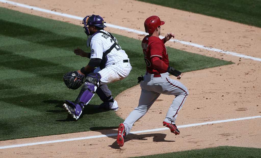 . Arizona Diamondbacks\' Chris Owings, right, heads to home plate to score on a single by Wade Miley as Colorado Rockies catcher Wilin Rosario fields the throw in the fourth inning of an MLB National League baseball game in Denver on Sunday, April 6, 2014. (AP Photo/David Zalubowski)