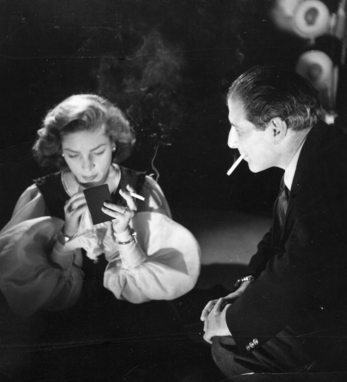 . 1951:  Lauren Bacall, the stage name of Betty Jean Perske a sultry American leading actress who started her career on the stage, making her film debut opposite Humphrey Bogart, whom she later married. She is sitting smoking and looking in a small hand mirror while the photographer Baron looks on.  (Photo by Baron/Getty Images)