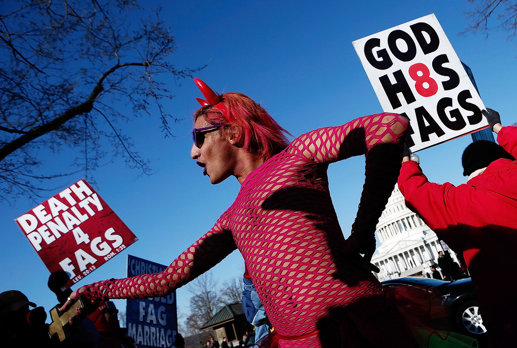 . New York based drag performer Queen dances during a rally while surrounded by protesters from the conservative Westboro Baptist Church in front of the U.S. Supreme Court on March 26, 2013 in Washington, DC. (Photo by Win McNamee/Getty Images)