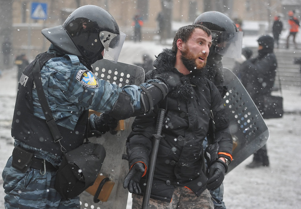 . Riot policemen arrest a protestor during an anti-government protest in downtown Kiev, Ukraine, 22 January 2014. Two protesters have died during violent clashes with police in Kiev, Ukrainian opposition activists said 22 January 2014.   EPA/ALEXEY FURMAN