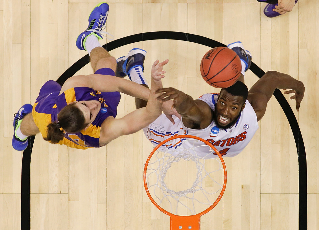 . Albany center John Puk, left, goes up for a rebound against Florida center Patric Young in the second half of a second-round game of the NCAA men\'s college basketball tournament in Orlando, Fla., Thursday, March 20, 2014. (AP Photo/John Raoux)
