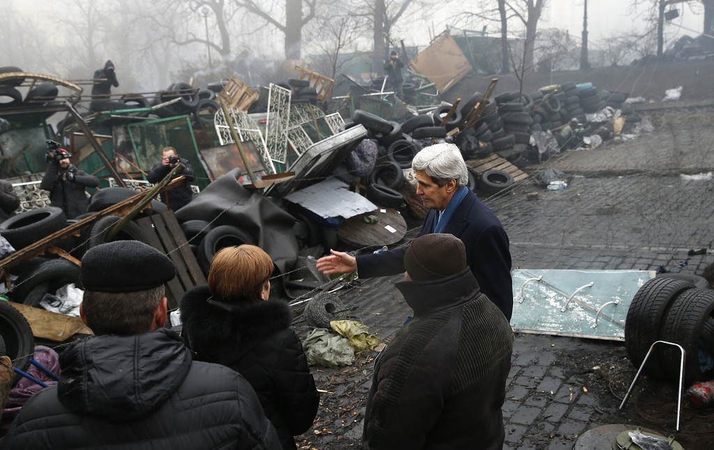 """. US Secretary of State John Kerry (2nd R) stands beside a barricade at the Shrine of the Fallen in Kiev on March 4, 2014. The Shrine of the Fallen, located on Institutska Street, honors the fallen \""""Heroes\"""" of the \""""Heavenly Sotnya\"""" (Hundred). AFP PHOTO / POOL - Kevin  LAMARQUE/AFP/Getty Images"""