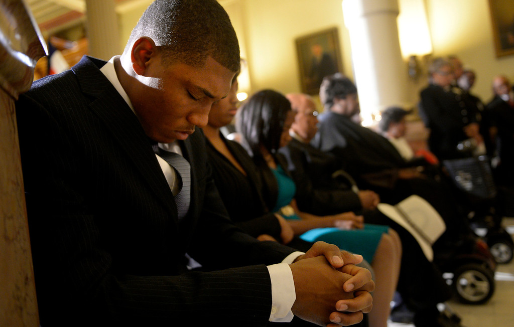 . Trent Rogers bows his head in prayer during a service for his father, former Lt. Gov. Joe Rogers, at the state Capitol in Denver, CO October 15, 2013. (Photo By Craig F. Walker / The Denver Post)
