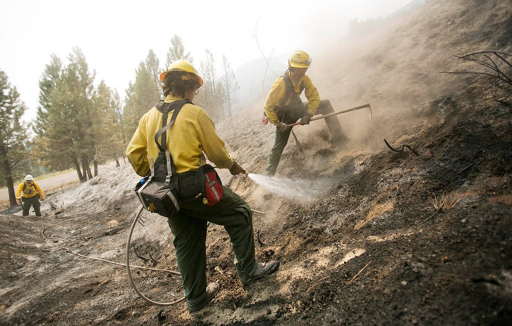 . Firefighters Nick Stone (right back, from Boise) and Matthew Younger (middle front, from Emmett), work to suppress hotspots near Dog Mountain in Pine, Idaho while fighting the Elk fire Wednesday Aug. 14, 2013.  (AP Photo/Idaho Statesman, Kyle Green)