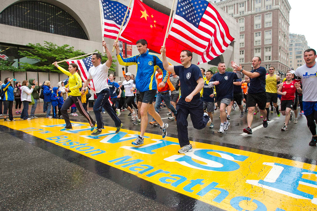 """. Runners holding American flags and a Chinese flag cross the finish line after completing the final mile of the Boston Marathon course during \""""#onerun\"""" in Boston, Massachusetts, May 25, 2013. The event was organized to give athletes and spectators an opportunity to complete the final mile of the Marathon that was cut short when two bombs exploded at the finish line.   REUTERS/Dominick Reuter"""