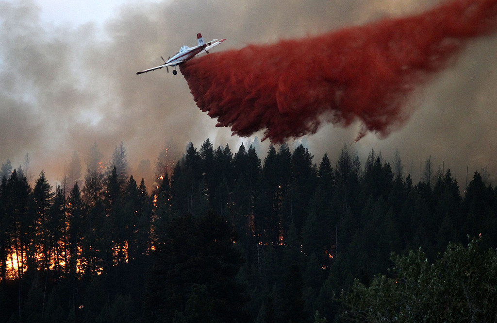. An air tanker drops fire retardant on the hillside overlooking Pine, Idaho while battling the more than 80,000 acres Elk Complex FIre on Sunday Aug.11, 2013. (AP Photo/Times-News,Ashley Smith)  Mandatory Photo Credit