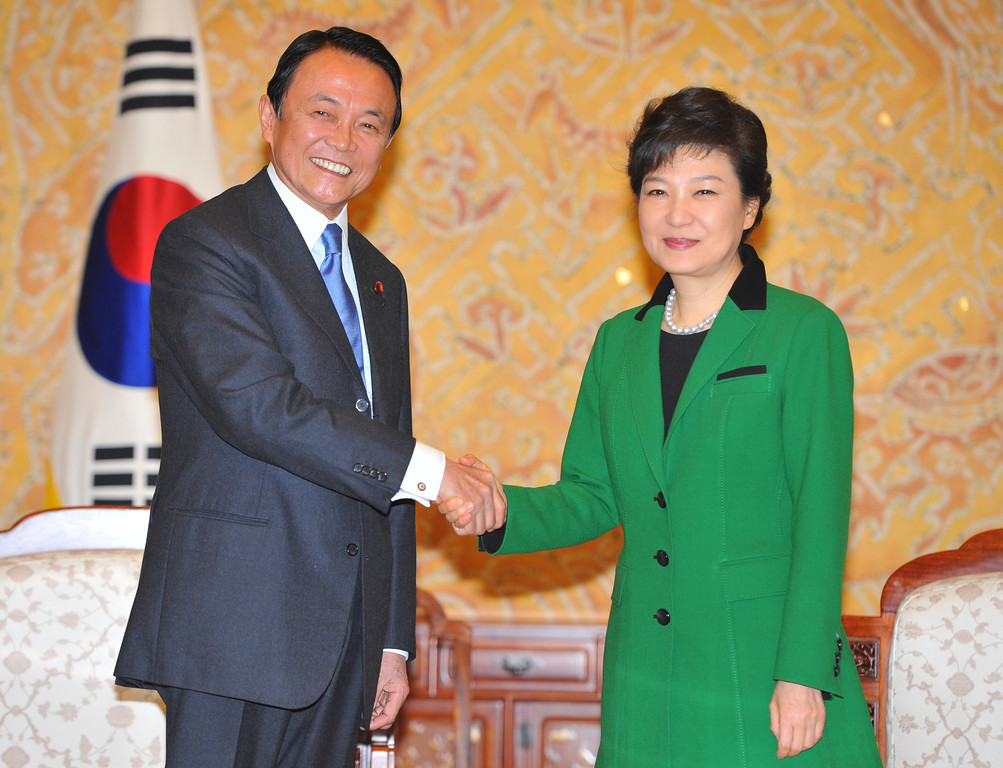 . South Korea\'s incoming president Park Geun-Hye (R) shakes hands with Japan\'s deputy prime minister Taro Aso at the presidential Blue House in Seoul on February 25, 2013. AFP PHOTO / POOL / KIM JAE-HWANKIM JAE-HWAN/AFP/Getty Images