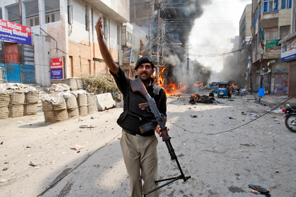 . A Pakistani police officer calls for help moments after a car bomb attack in Peshawar, Pakistan, Sunday, Sept. 29, 2013. (AP Photo/Mohammad Sajjad)