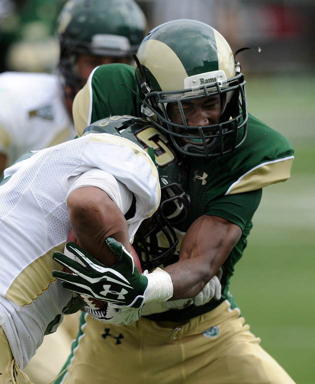 . FORT COLLINS, CO. - SEPTEMBER 14: Rams\' defensive back DeAndre Elliott (13) wrapped up Cal Poly split back Kristaan Ivory (5) in the second half. The Colorado State University football team defeated Cal Poly at Hughes Stadium in Fort Collins Saturday afternoon, September 14, 2013.  It was the Rams\' first home game and first win of the season. Photo By Karl Gehring/The Denver Post